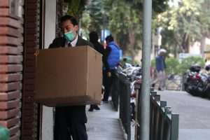 A man in a suit wearing a mask and carrying a box representing an employee let go during the pandemic