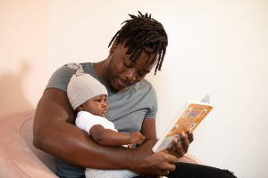A father holding his baby representing an employee who cannot return to work due to childcare issues